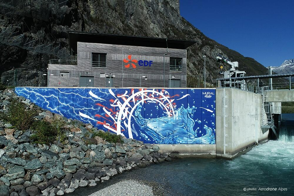 """Fresque murale sur ouvrage hydroélectrique EDF - Réalisée par <a href=""""https://mural-studio.fr"""" target=""""_blank"""" rel=""""noopener noreferrer"""">Mural Studio</a><br/> Acrylique et aérosol - 70 m2 env.<br/> Gavet (38) - 2019 - <em><a href=""""https://etien.fr/fresque-murale-barrage-edf/"""" target=""""_blank"""" rel=""""noopener noreferrer"""">voir + de photos</a></em>"""
